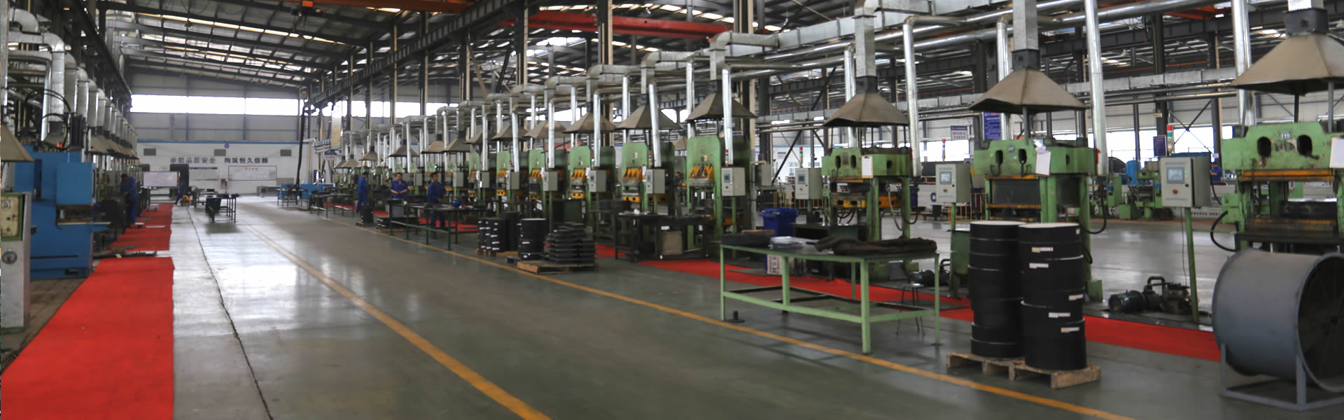 A large workshop with bridge bearing products and equipment in it.